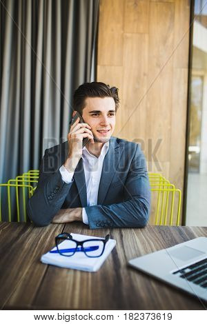 Young Businessman In An Office Speaking On His Phone With Note Paper In Front Of Him