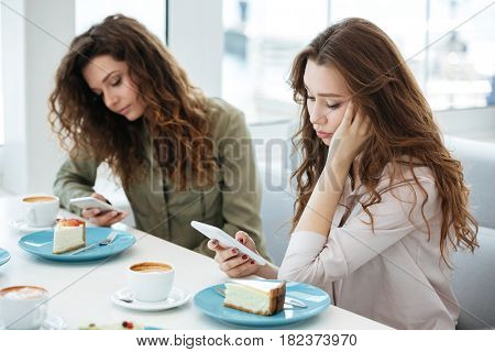 Side view of a two women sitting by the table and using smartphones in cafe