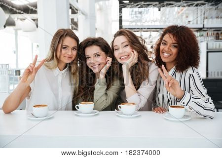 Four young smiling friends sitting by the table in cafe and looking at the camera