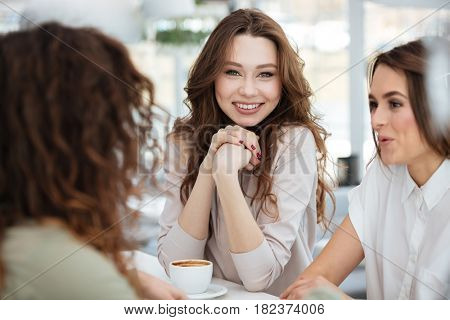 Smiling brunette woman sitting by the table with her three friends in cafe