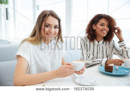 Side view of two young pretty friends sitting by the table in cafe