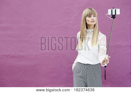 Pretty young woman posing for cell phone against pink