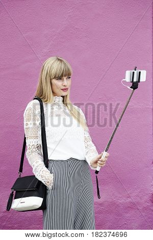 Stylish young woman posing for selfie with selfie stick