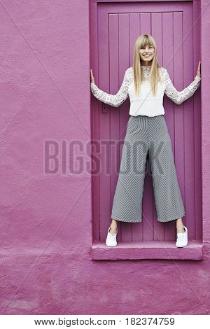 Gorgeous young blond woman standing in pink doorway