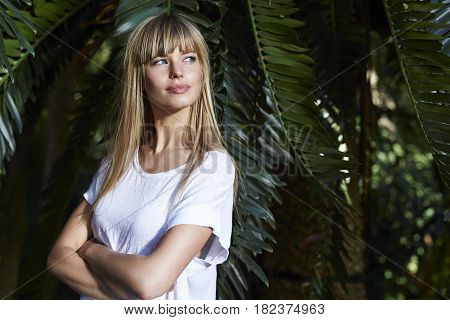 Blond beautiful woman by palm tree looking away
