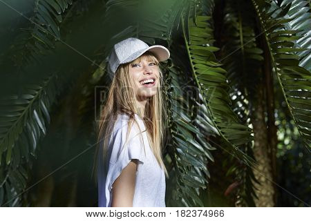 Vivacious young blond woman by palm tree portrait