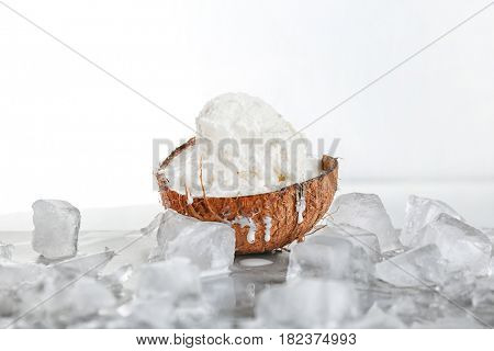 Fresh ball of ice cream in half of coconut and icy cubes on white background