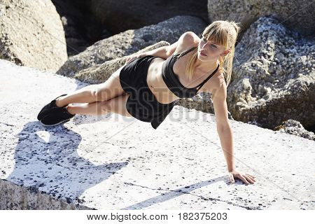 Strong young athlete balancing in sportswear on rocks