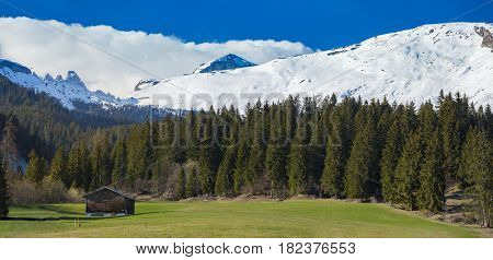 Swiss Alps pastoral landscape with hut by the beginning of spring