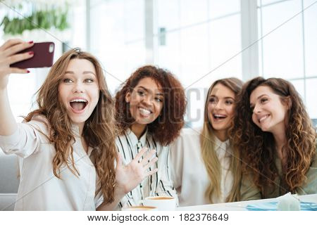 Four friends sitting by the table in cafe and making selfie on smartphone