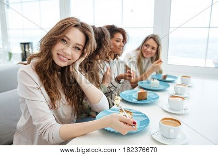 Side view of a Four young friends sitting by the table in cafe and eating cakes