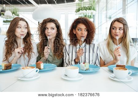 Four mystery friends sitting by the table in cafe and eating cakes