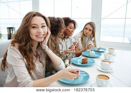 Side view of a Four smiling friends sitting by the table in cafe and eating cakes