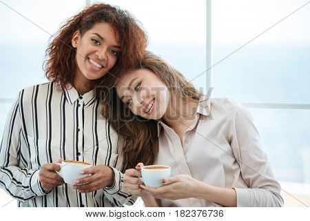 Two smiling women sitting near the window in cafe and looking at the camera