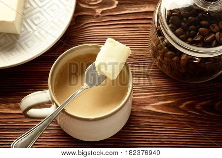 Cup of tasty butter coffee and shovel on wooden table