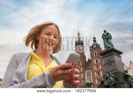 Female tourist in a yellow dress stands on a background of the church of St. Mary in Krakow with a phone. Basilica Mariacka. Krakow. Poland.