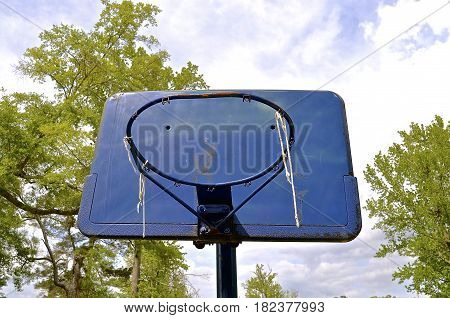 A bent rim, a missing net, and blue backboard display the memories of outdoor basketball
