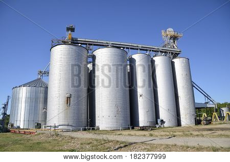 A cluster of grain elevator, bins, and silos for storing grain and corn