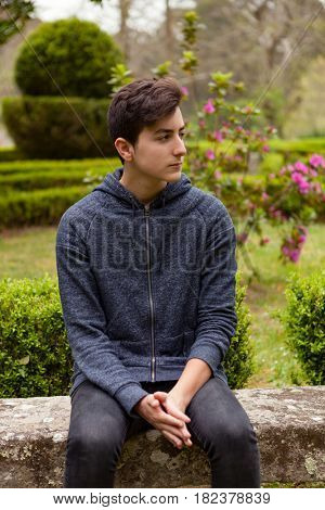 Pensive teenager guy with fifteen years old in a park