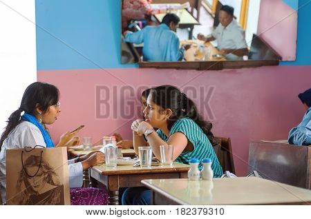 BANGALORE, INDIA - FEB 11, 2017: Young women talking and having dinner in popular indian cafe with colorful interior on February 11, 2017. Capital of the state Karnataka has a population of 8.42 million