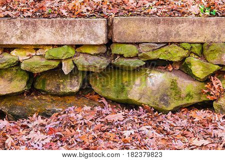 The rough stone wall in the autumn park with dry leaves