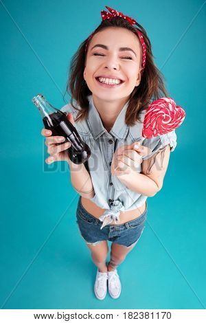 Picture of happy young lady standing and posing isolated over blue background. Eating candy and holding aerated sweet water.