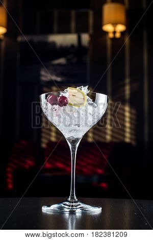 glas of water with ice and lime on a black background