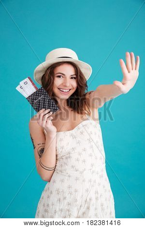 Portrait of a smiling young girl traveller holding passport and travelling tickets and waving goodbye isolated over blue background