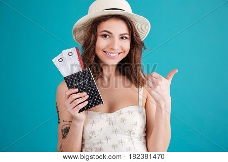 Close up portrait of a smiling happy woman traveller in summer clothes holding passport with plane tickets and showing thumbs up gesture isolated over blue background