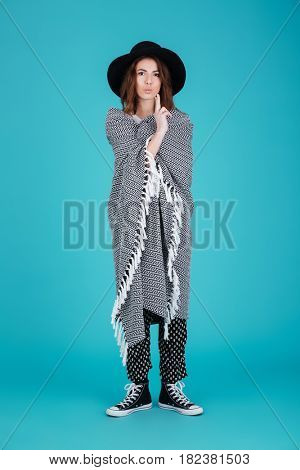 Full length portrait of a young funny woman in hat covered in blanket standing isolated over blue background