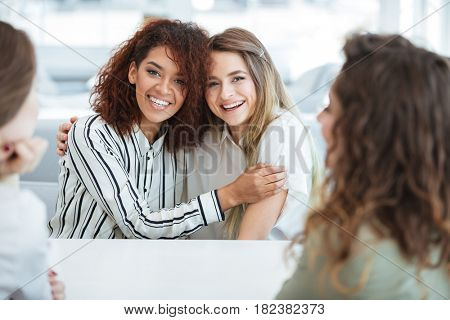 Two happy women hugging and sitting by the table with their friends in cafe