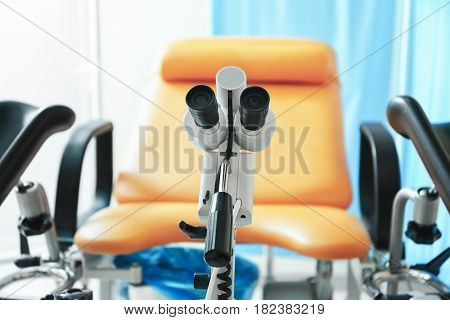 Colposcope in gynecological room and blurred chair on background
