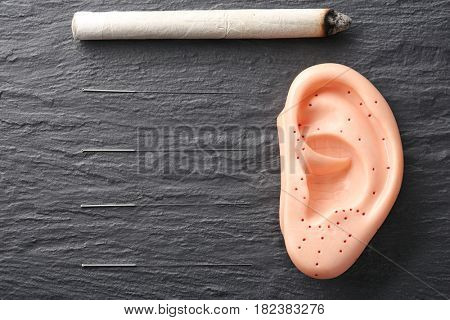 Moxa stick, needles for acupuncture and plastic mockup of human ear on dark textured background
