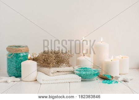 Spa composition with candles sea salt and flowers on white wooden background.