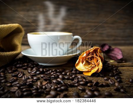 Coffee cup and coffee beans with rose on table
