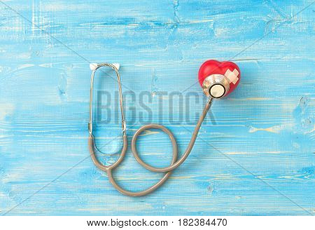 One single alone red heart love shape hand exercise ball with bandage MD medical doctor physician's stethoscope blue wood background