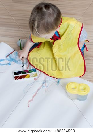 The kid in a yellow waistcoat draws a brush on a white paper with watercolors and sits on the floor