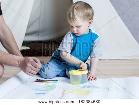A cute kid dunks a brush in a plastic glass with water before that either draw