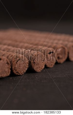 Close up of chocolate waffle rolls in a row over wooden surface