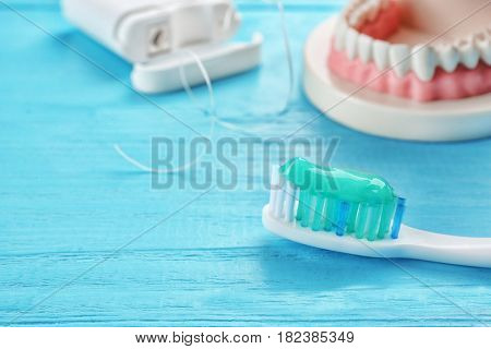 Toothbrush with paste on color wooden background, closeup