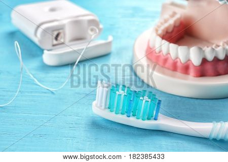 Toothbrush, dental floss and plastic jaw mockup on color wooden background, closeup