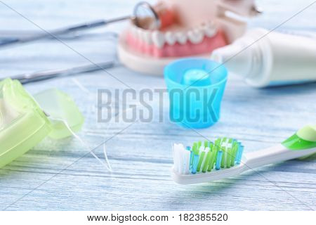 Toothbrush and dental floss on wooden background, closeup