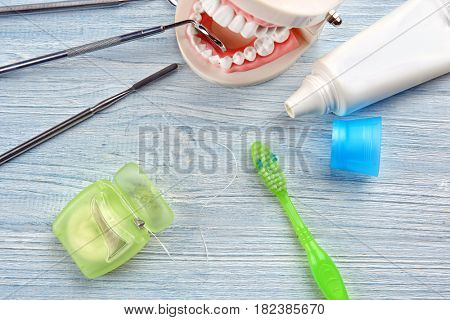 Dental instruments and set for teeth cleaning on wooden background, closeup