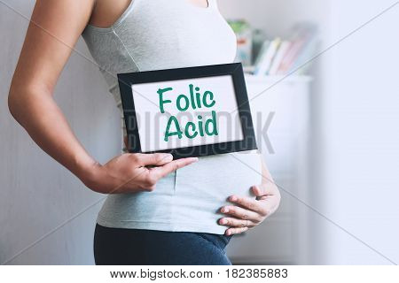 Pregnant woman holds whiteboard with text message - FOLIC ACID. Pregnancy parenthood preparation and expectation concept. Close-up copy space indoors.