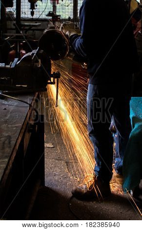 Craftsman uses angle grinder to cut piece of wrought iron metal with sparks flying and protective industrial gloves in workshop