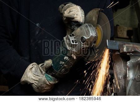 Craftsman uses angle grinder to cut piece of wrought iron metal with sparks flying and protective industrial gloves