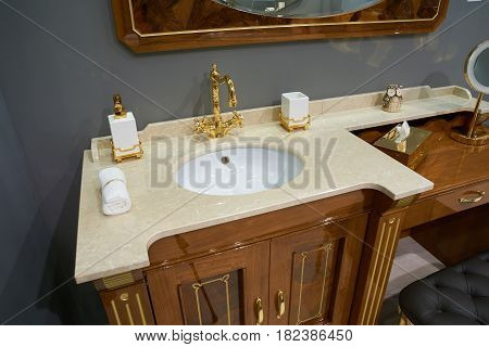 View on luxury bathroom with white inset ceramic washbasin with glossy gold plated metal mixer and accessories