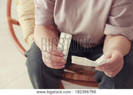 Elderly woman with pills and instruction at home, closeup