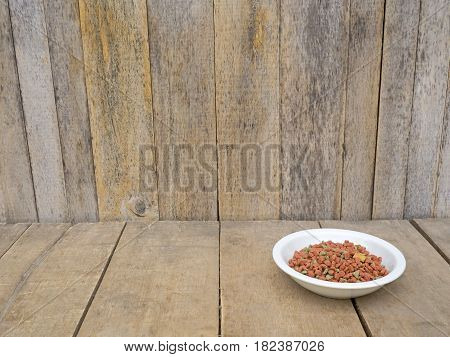 Dog food in bowl on wooden table wood as a background