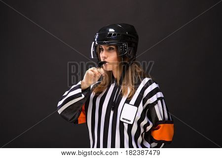 ice hockey referee-woman blows the whistle black background